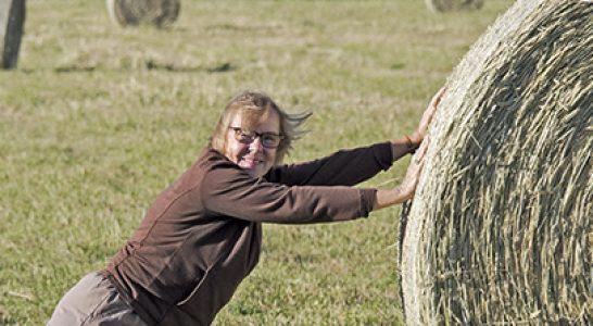 Christine rolling hay bale